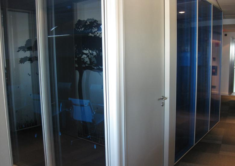 Reflejo del árbol en la cristalera coloreada en azul del despacho principal.